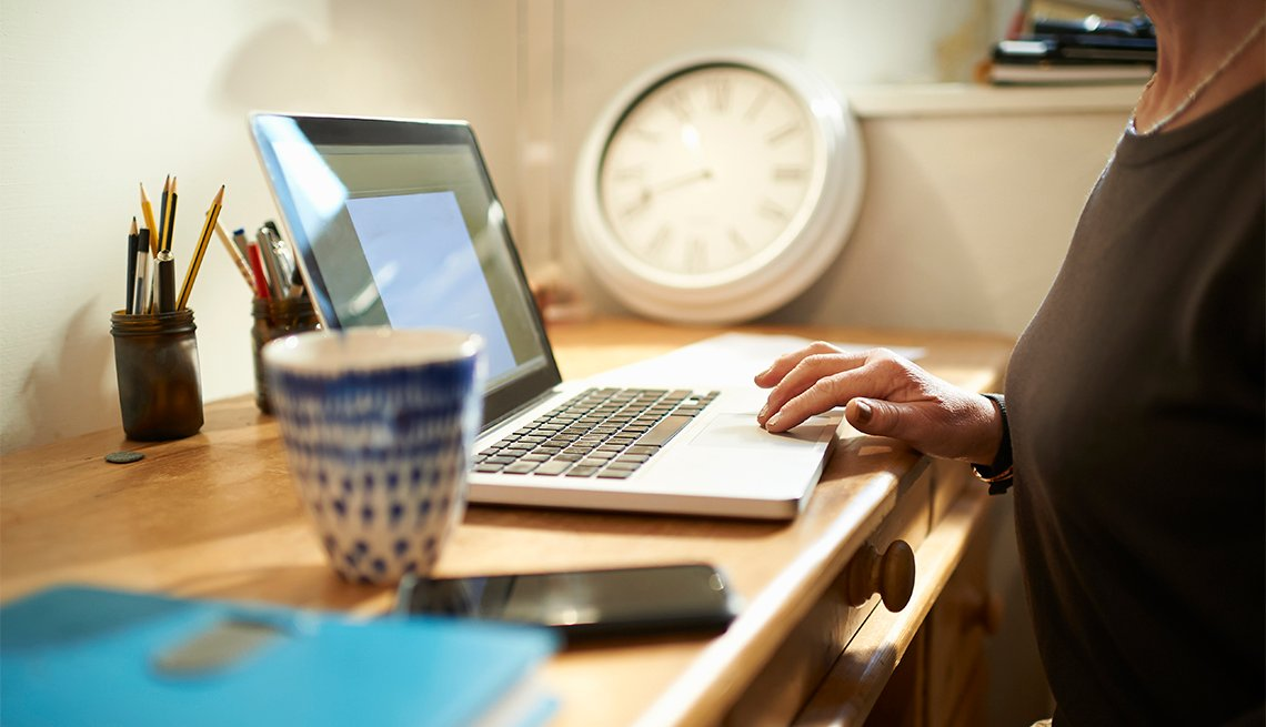 A woman sits at a desk at home with a hot drink and phone and uses a laptop, close up