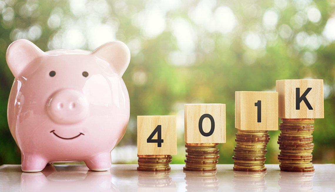 Alcancía rosada de cochinito al lado de monedas apiladas que sostienen cubos que dicen 401k