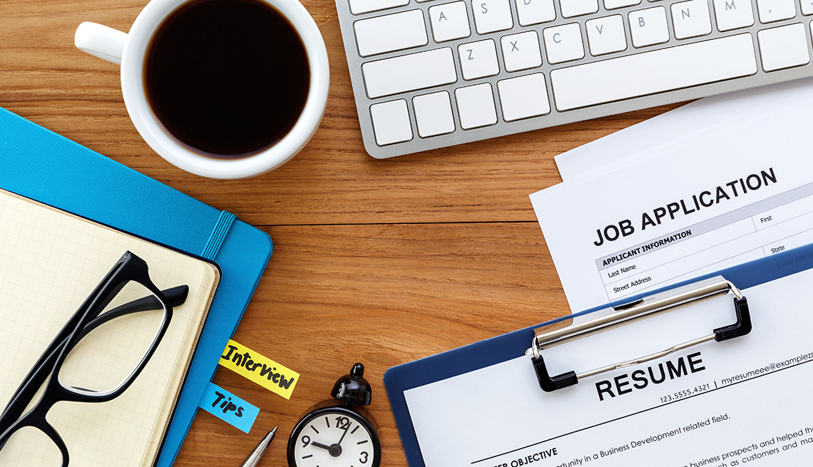 An application and resume sit on a desk with coffee and a keyboard
