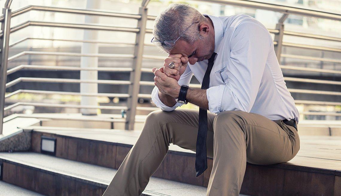 Hombre sentado en unas escaleras en la calle mientras sostiene su cabeza en una mano empuñada.