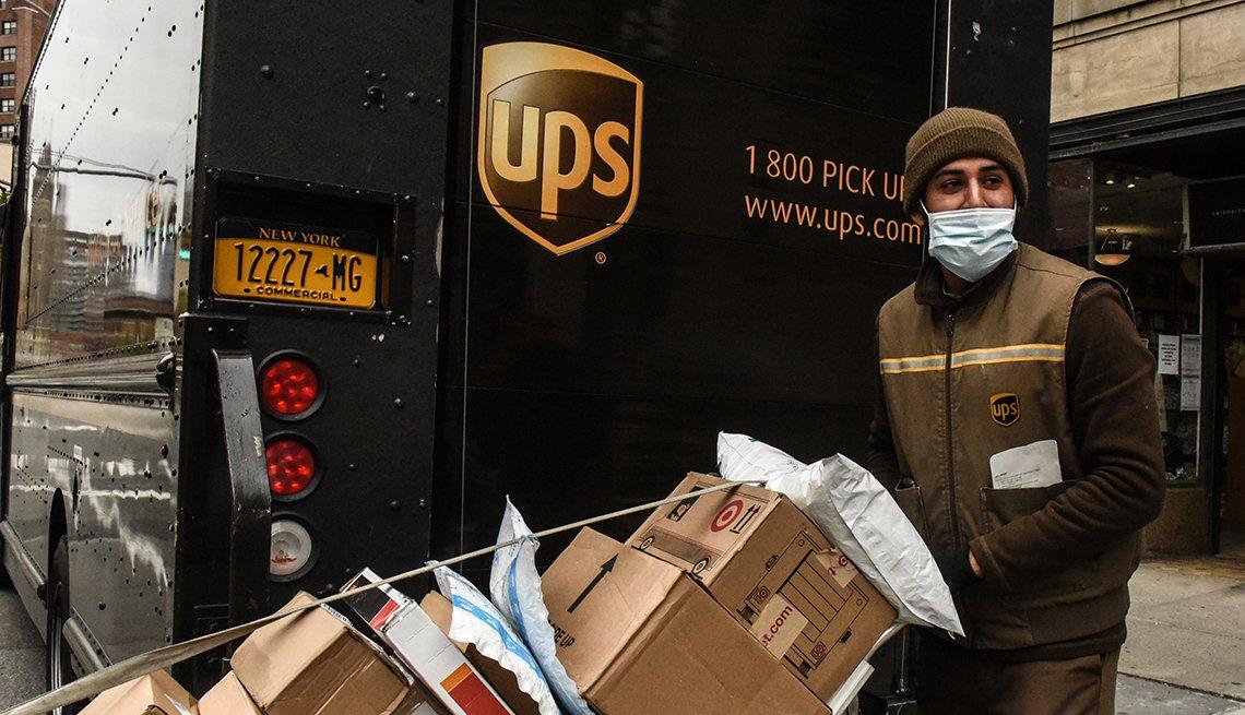 Conductor de UPS con varios paquetes para entregar.