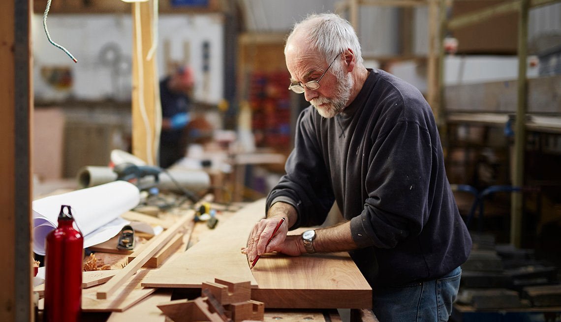 an older man is working with wood at a shop