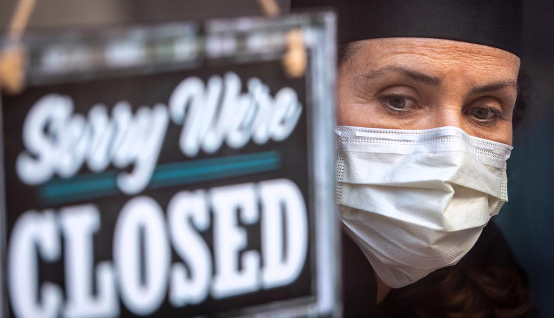 Empleada de un restaurante usando mascarilla al lado de un letrero que dice, lo sentimos está cerrado.