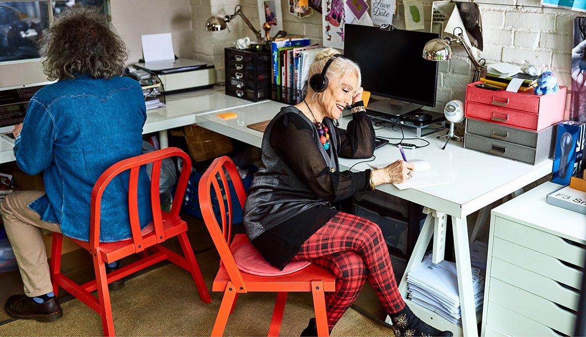 Dos mujeres trabajando desde la oficina de su casa. Una en la computadora y la otra hablando por teléfono.