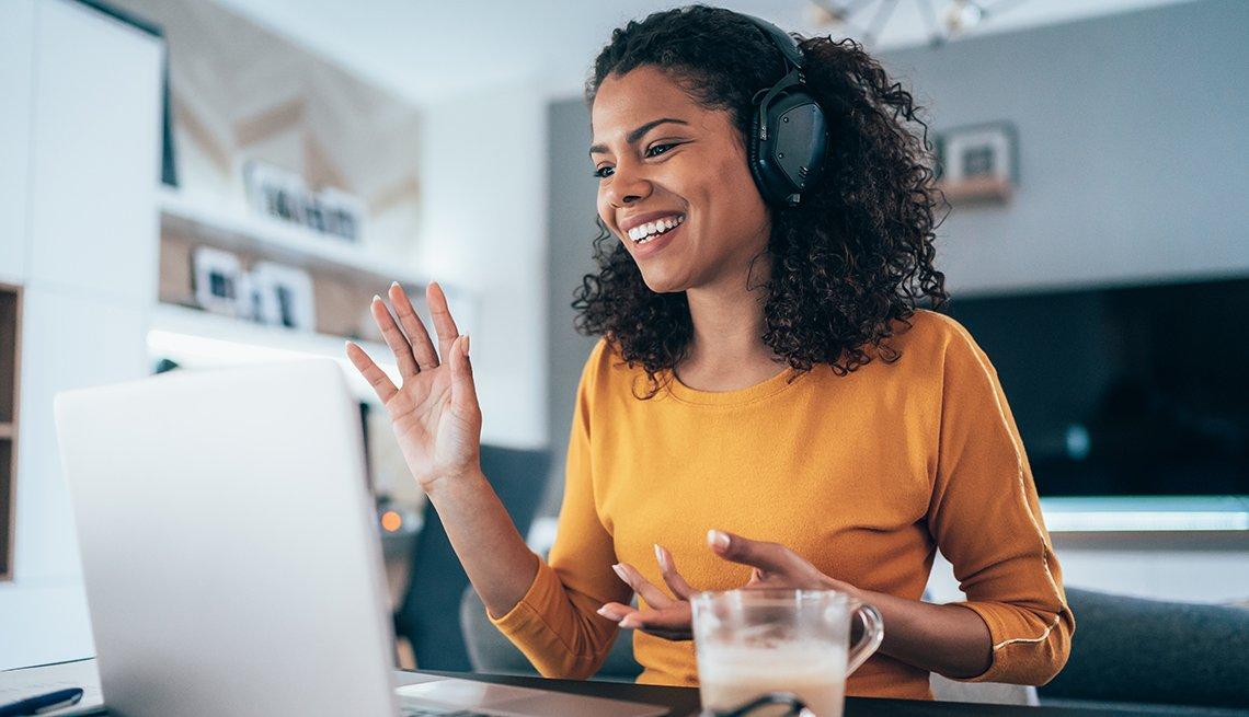 Mujer participando en una videoconferencia desde su computadora en casa.