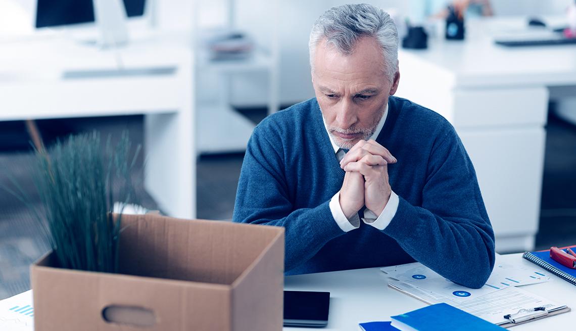 Hombre con una caja encima de su escritorio de trabajo