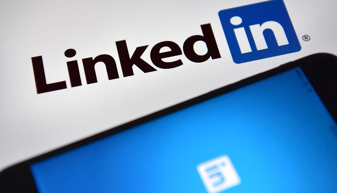 Logo de LinkedIn al lado de un móvil que muestra la aplicación de la compañía