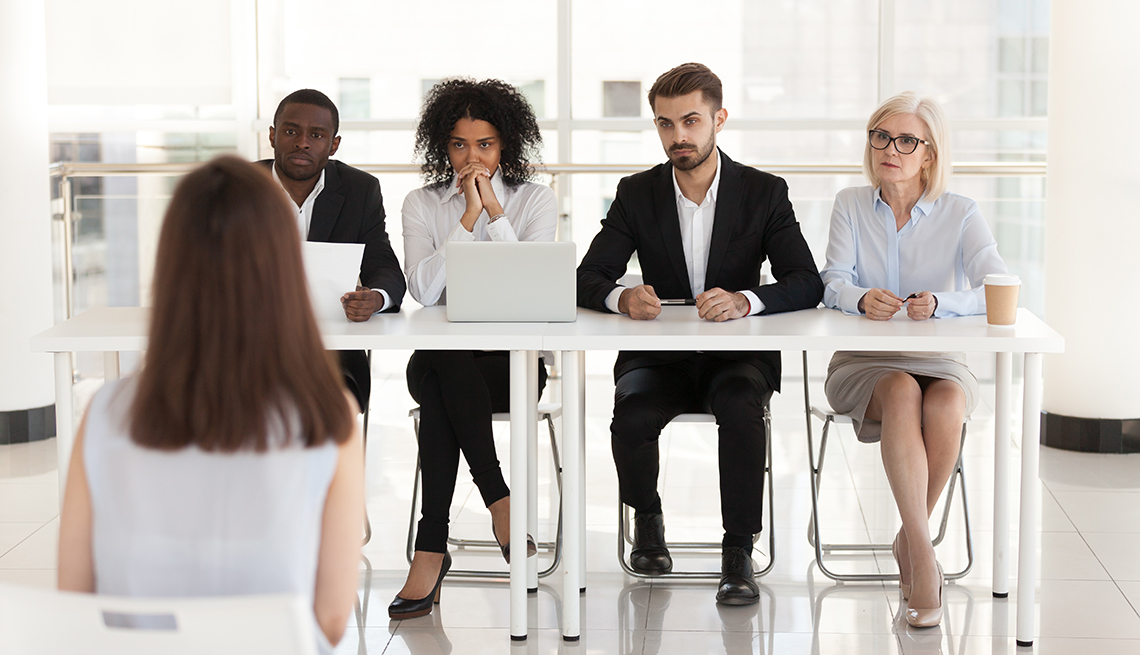 A group of people sitting at a table interviewing a woman