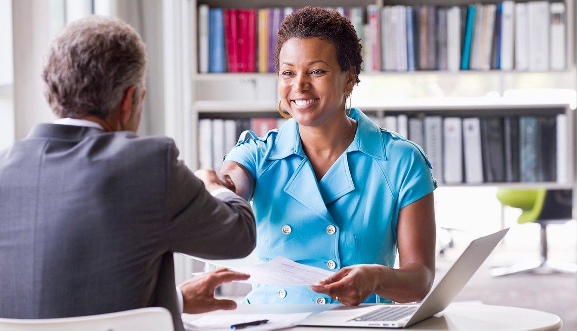 Mujer y hombre se dan un saludo de manos en una oficina
