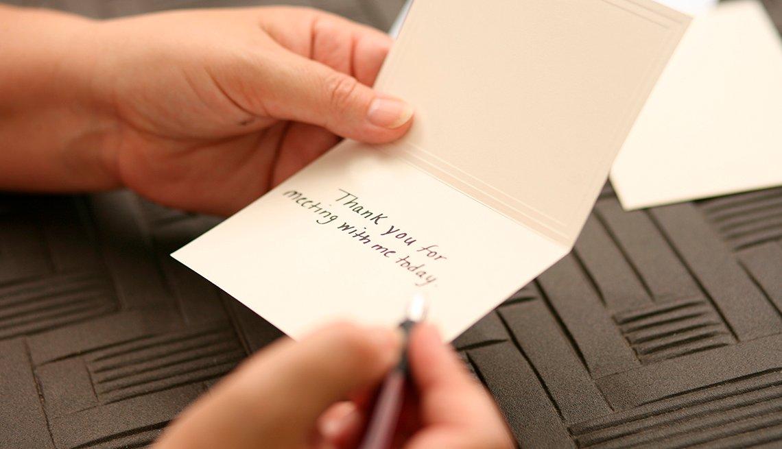 Persona escribiendo una nota de agradecimiento