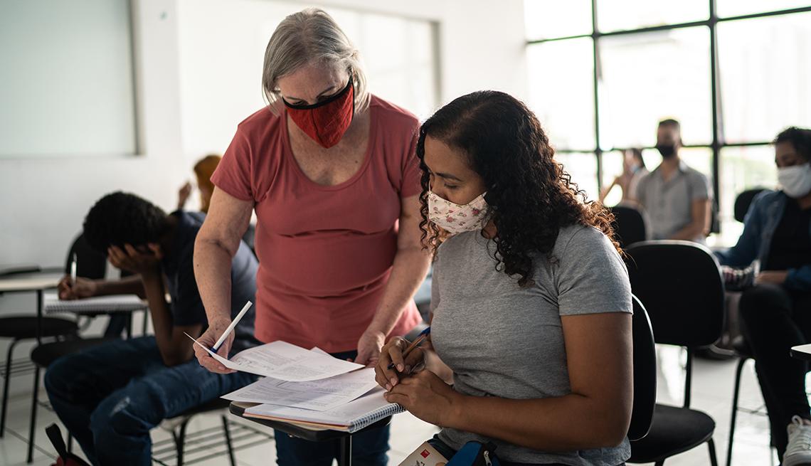Profesora ayuda a un estudiante en un salón donde todos están con mascarilla