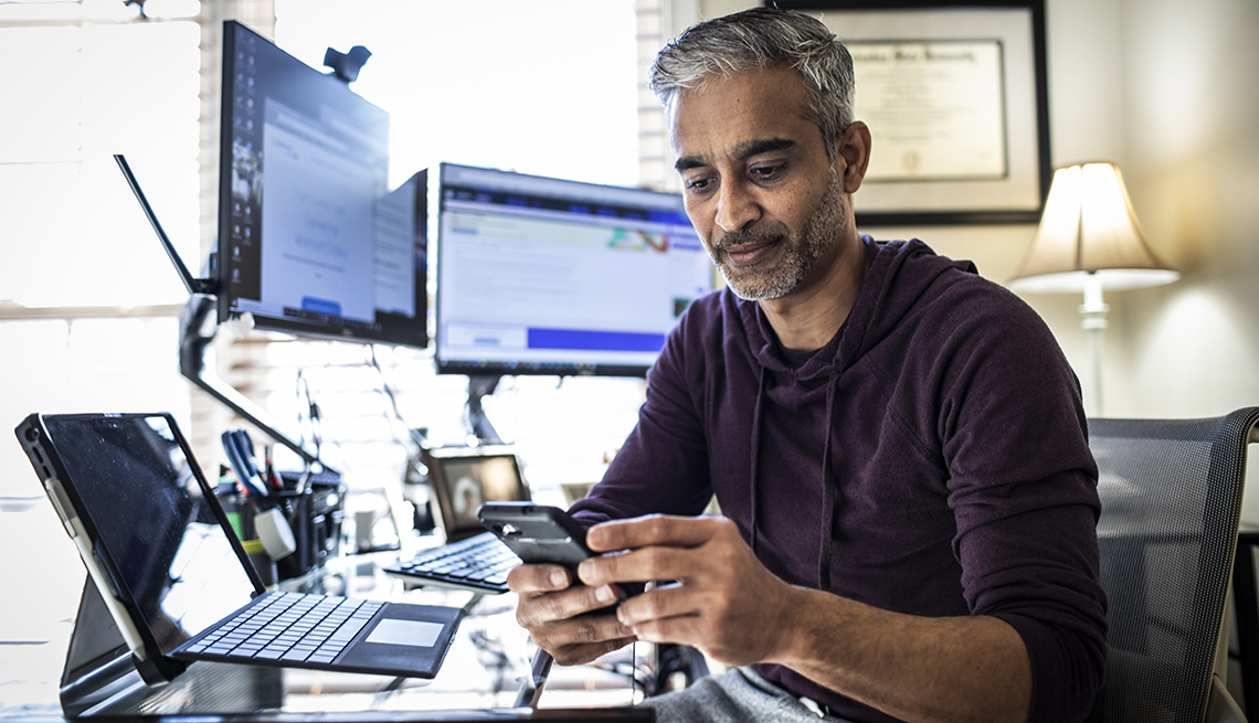 Hombre trabajando desde su casa con dos monitores, una computadora portátil y mirando un teléfono móvil.