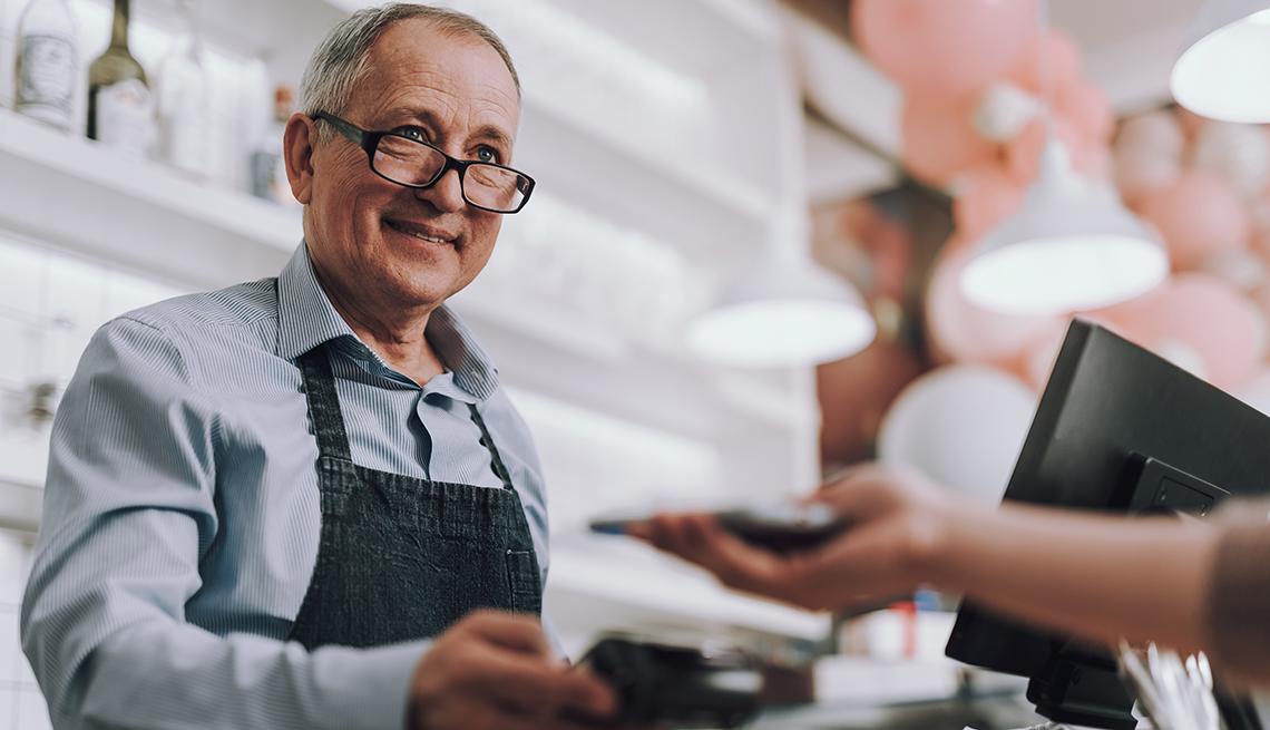 Hombre mayor trabajando como cajero en una tienda atiende a una cliente