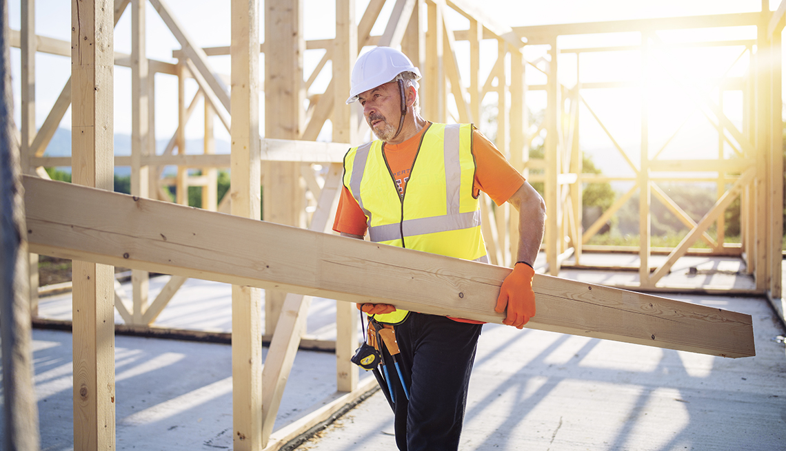 A construction worker holding a wooden beam