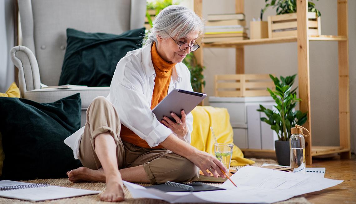 Mujer sentada en el suelo mientras trabaja en la sala de su casa