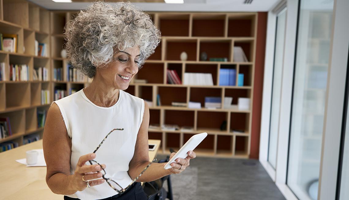 Mujer en una oficina mira su teléfono móvil que sostiene en la mano.