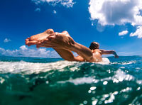 Lisa Bedient paddles her surfboard while surfing on Kauai, Hawaii.