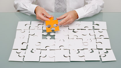 Businessman holding jigsaw piece.