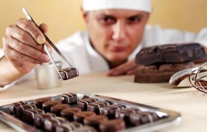Cocinero hacer dulces de chocolate en una cocina