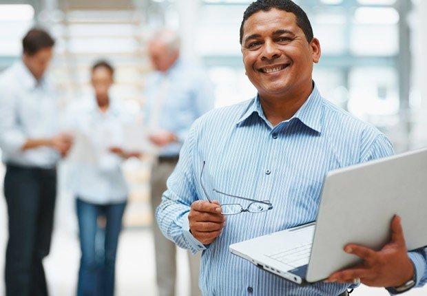 Hombre con un computador portátil en la mano - 10 consejos para asistir a una Feria de Empleo Virtual