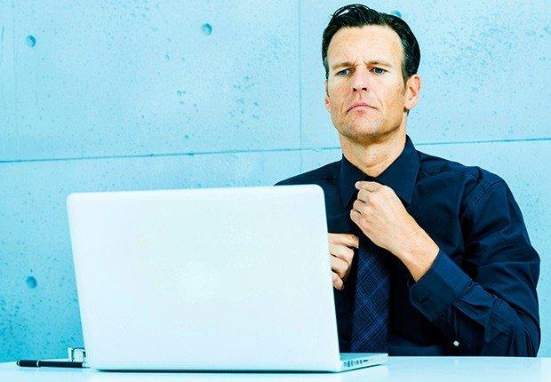Hombre arreglándose la corbata al frente de un computador - 10 consejos para asistir a una Feria de Empleo Virtual