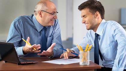 Un joven jefe habla con un hombre de negocios de más edad en una oficina, Trabajando para un jefe más joven