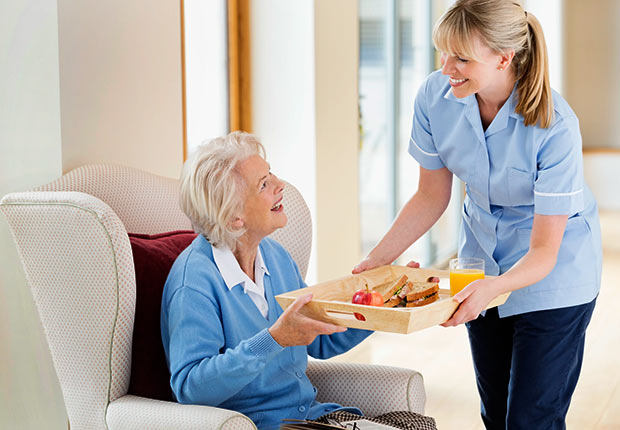 Caregiver giving older woman tray of food, Growing Jobs 2014