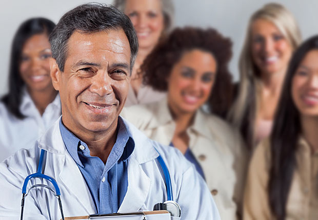Hispanic doctor standing in front of a group, Growing Jobs 2014