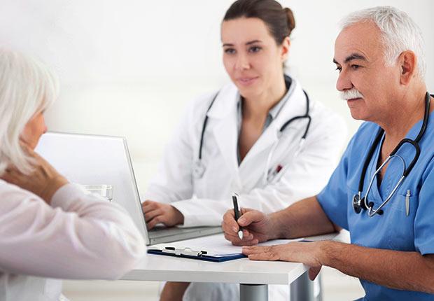 Doctors with assistants and senior patient, Growing Jobs 2014