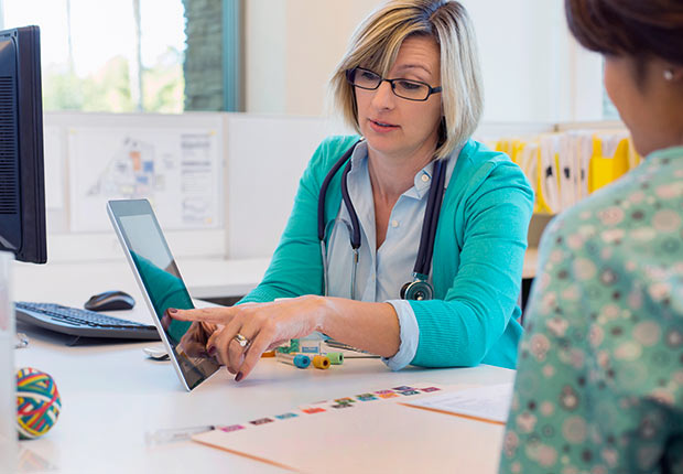 Female doctor reviewing medical records with nurse at desk, Growing Jobs 2014