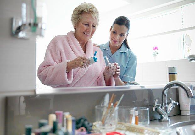 Enfermera ayudando a lavarse los dientes de su paciente - Trabajos de gran demanda en el 2014
