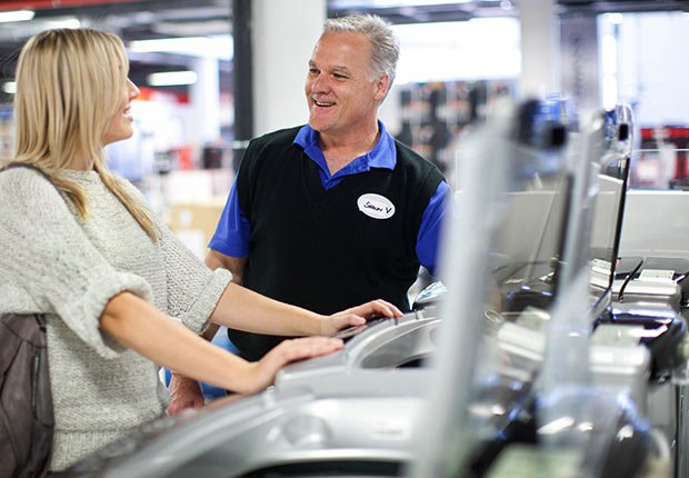 Young woman and salesman negotiating in showroom , Growing Jobs 2014