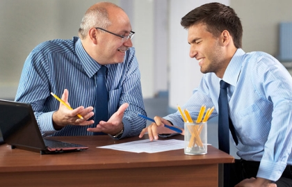 A young boss talks with an older businessman in an office, Working for younger boss