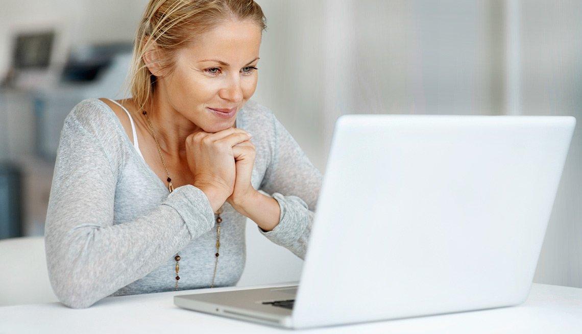Mujer con expresión de felicidad mientras mira una computadora.