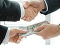 Dos hombres estrechando la mano e intercambiando dinero.