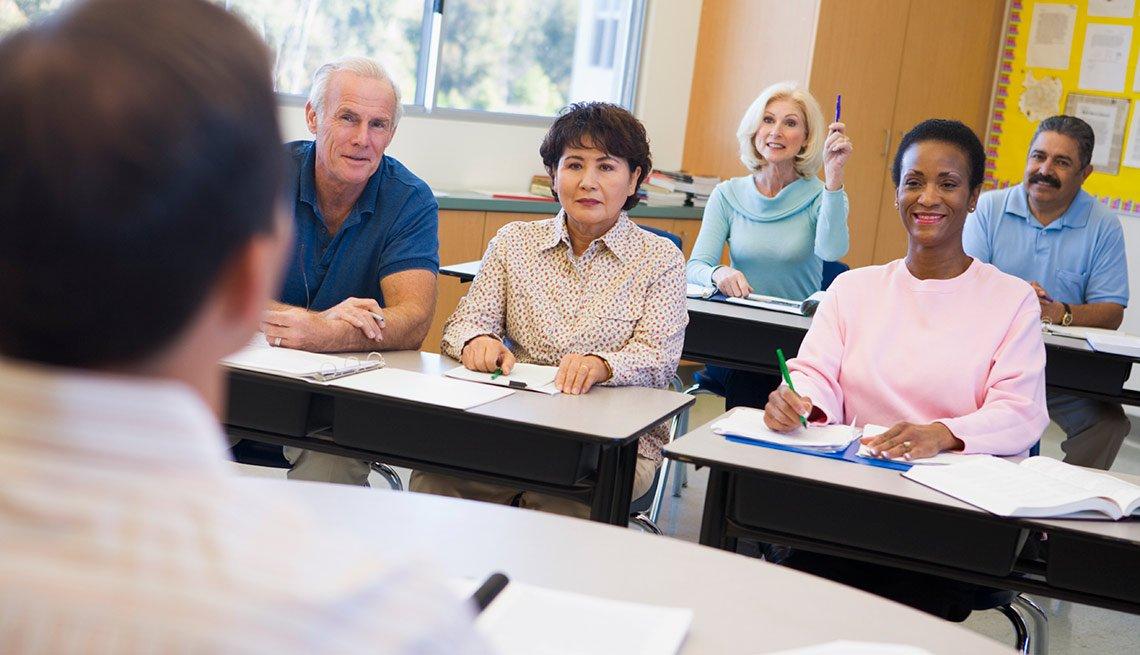 Kick Start Your Career - Mature female student raising hand in class