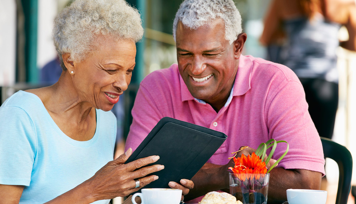 Senior Couple Using Tablet Computer At Outdoor Café, AARP TEK Academy