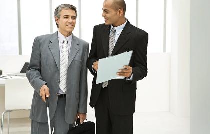 Hombre con discapacidad visual en traje de corbarta con un hombre al lado - Consejos para la búsqueda de trabajo con discapacidades visuales