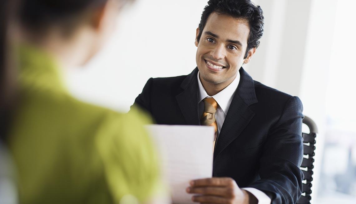 Hombre en traje mirando a otra persona, sonriendo y sosteniendo un papel en la mano - Preguntas difíciles de la entrevista de trabajo