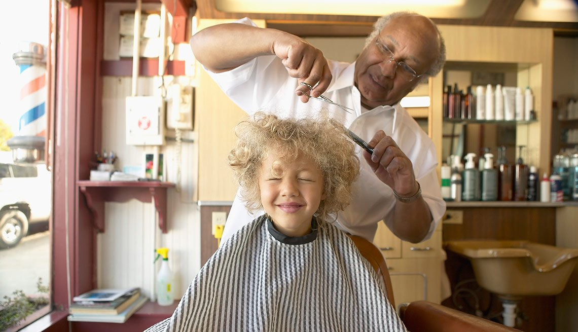 Barber cuts young girl's hair, Hair stylist is a job that makes people feel and look good