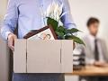 Hombre con una caja llena de objetos personales en las manos mientras camina en una oficina - Errores que afectan tus beneficios de desempleo