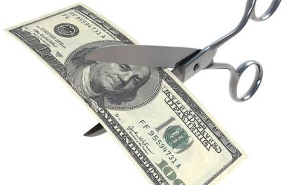 Un billete de 100 dólares y unas tijeras a punto de cortarlo - Considerar el recorte de salario
