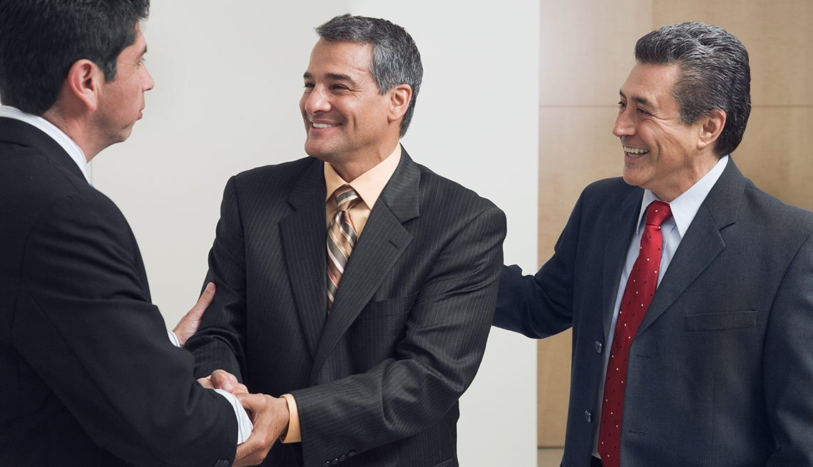 Tres hombres con traje estrechando las manos y sonriendo - Un nuevo comienzo