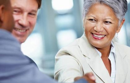 Mujer mayor estrechando la mano de un hombre - Cómo buscar empleo en el mercado laboral