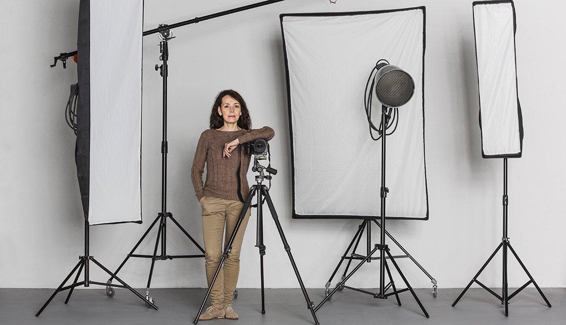 Fotógrafa en un estudio con luces y cámara