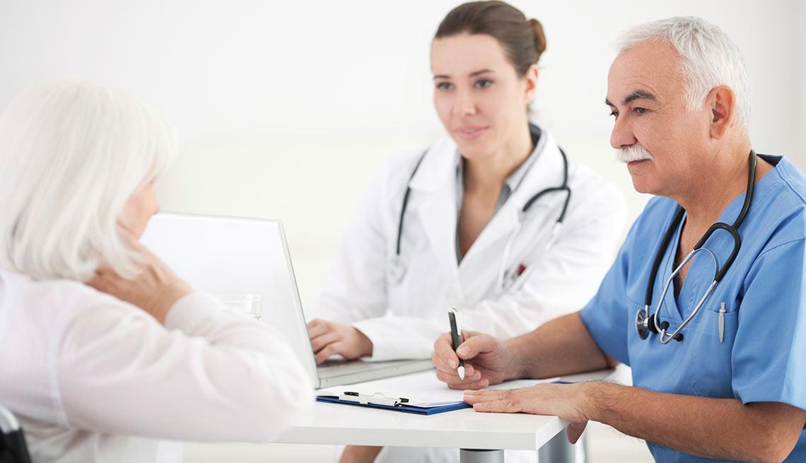 Médico con un asistente en consulta con paciente, crecimiento de empleos
