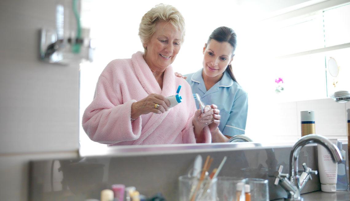 Enfermera ayudando a una mujer a lavarse los dientes, crecimiento de empleos