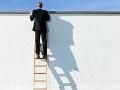 Hombre subido en una escalera viendo a través de un muro, estará preparado para su segunda carrera.