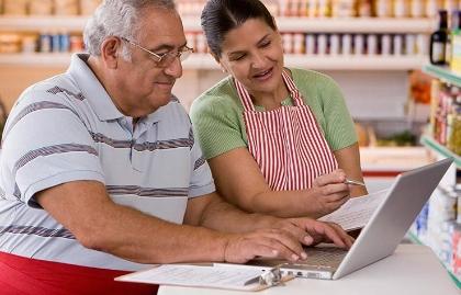 Una pareja mayor hace las cuentas de su negocio frente a una computadora