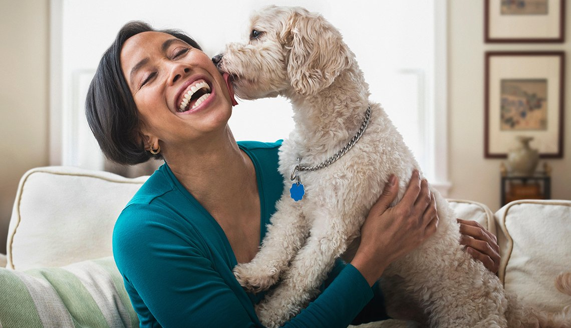 a woman gets a kiss from a dog she's pet boarding for the summer